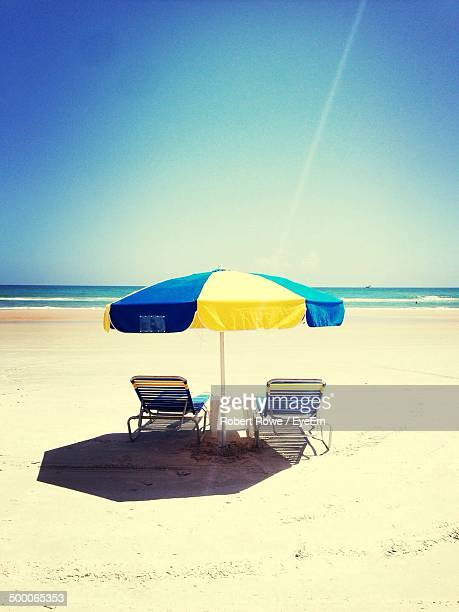 Lounge chairs under umbrella at beach