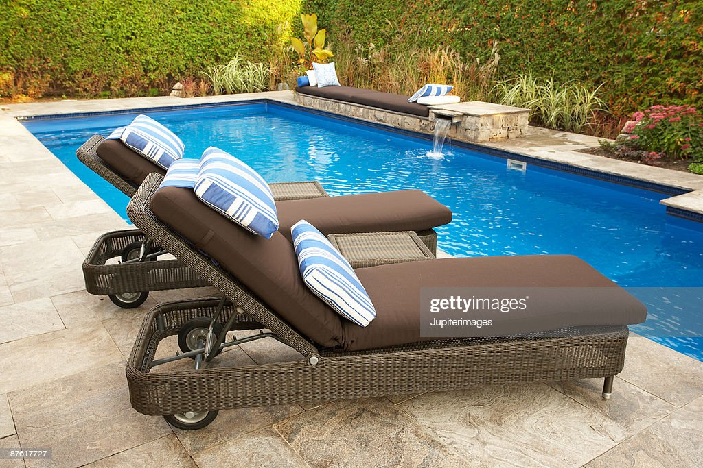 Lounge Chairs With Pillows Next To Swimming Pool Stock-Foto ...