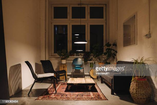 lounge room in an office at night - living room stock-fotos und bilder