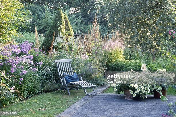 Lounger on stone patio surrounded by mixed borders, Tor de linden, Holland