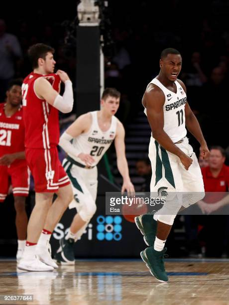 Lourawls Nairn Jr #11 of the Michigan State Spartans celebrates the win at the buzzer as Ethan Happ of the Wisconsin Badgers reacts during...