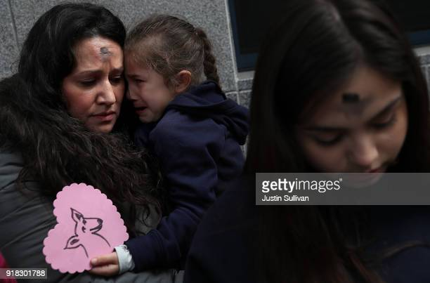 Lourdes Barraza wife of detained immigrant Fernando Barraza holds her crying daughter Ana Barraza during a Valentine's Day demonstration outside of...