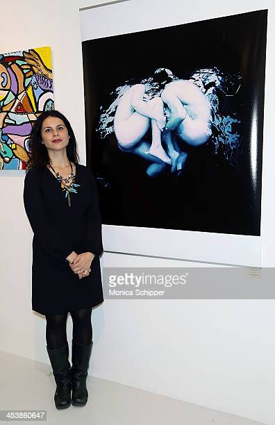 Lourdes DeLa Cruz poses with her husband Francisco Uceda's work at 'love art give a smile' Art Fashion And Design Benefit at Clen Gallery on December...