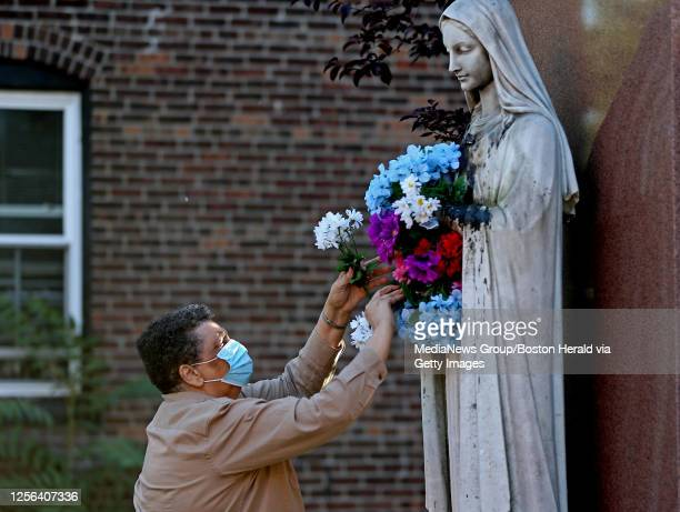 """Lourdes Gomes adds flowers to the Virgin Mary statue that was vandalized recently in preparation for a rosary prayer service at the St Peter""""u2019s..."""