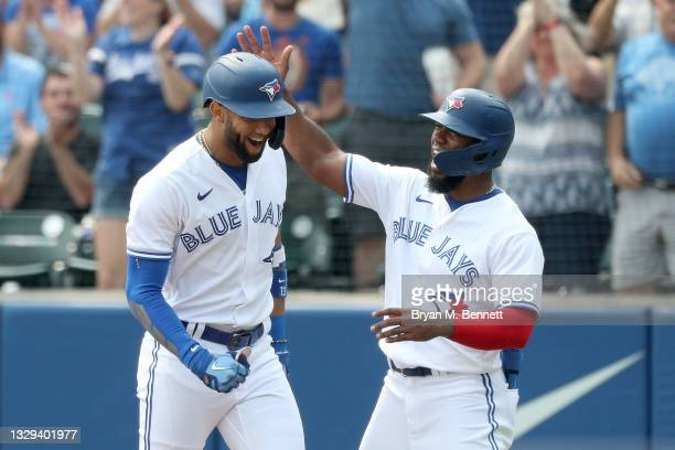 Lourdes Gurriel Jr. #13 of the Toronto Blue Jays celebrates with teammate Teoscar Hernandez after hitting a grand slam home run during the first...