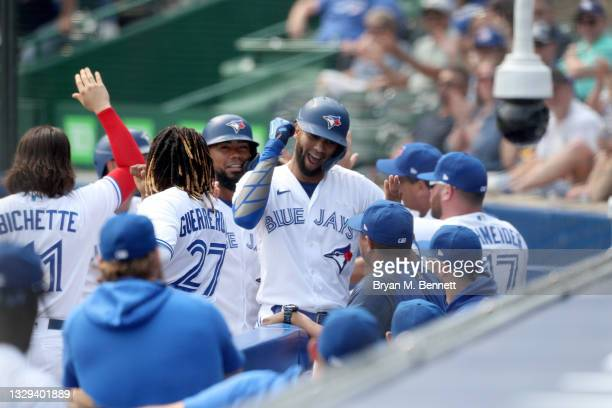 Lourdes Gurriel Jr. #13 of the Toronto Blue Jays celebrates with teammates after hitting grand slam home run during the first inning in game two of a...