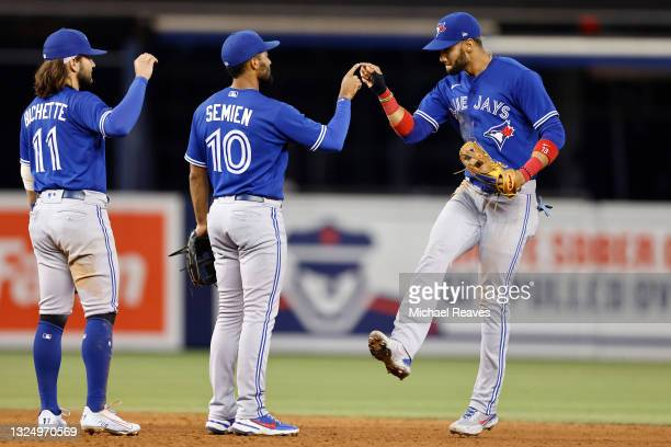 Lourdes Gurriel Jr. #13 of the Toronto Blue Jays high fives Marcus Semien and Bo Bichette after defeating the Miami Marlins 2-1 at loanDepot park on...
