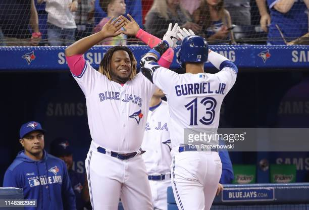 Lourdes Gurriel Jr #13 of the Toronto Blue Jays is congratulated by Vladimir Guerrero Jr #27 after hitting a solo home run in the fourth inning...