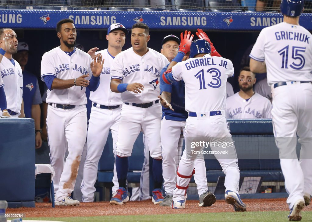 Lourdes Gurriel Jr. #13 of the Toronto Blue Jays is congratulated by Marcus Stroman #6 after hitting a two-run home run in the eighth inning during MLB game action against the New York Mets at Rogers Centre on July 3, 2018 in Toronto, Canada.