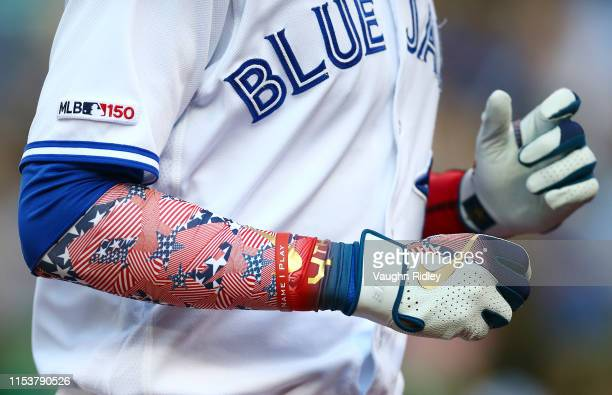 Lourdes Gurriel Jr #13 of the Toronto Blue Jays wears Stars and Strips gloves and arm sleeve for the 4th of July holiday in the first inning during a...