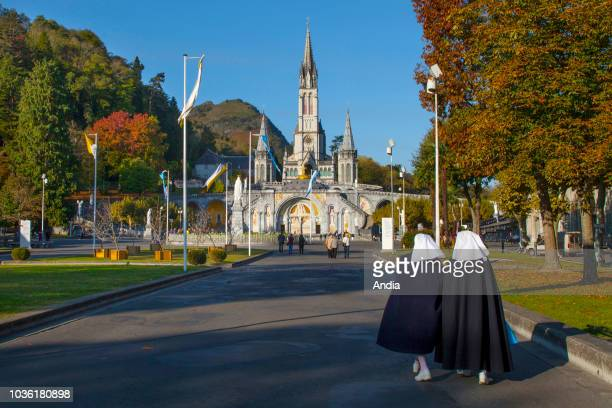 Lourdes : outer view of the Basilica of Our Lady of the Rosary, the square and Our Lady of Lourdes sanctuary. Two nuns walking towards the basilica