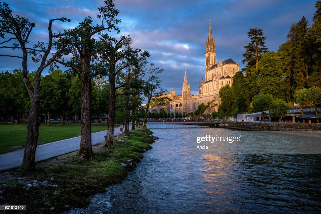 Lourdes (south-western France). The Basilica of Our Lady of the Rosary, built above the Grotto of Massabielle, viewed at sunset from the banks of the Gave de Lourdes river.