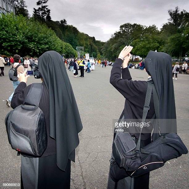Lourdes, visit of Pope Benedict XVI , two nuns taking pictures of the Grotto of Massabielle. 2008 is the year of the 150th anniversary of Virgin...