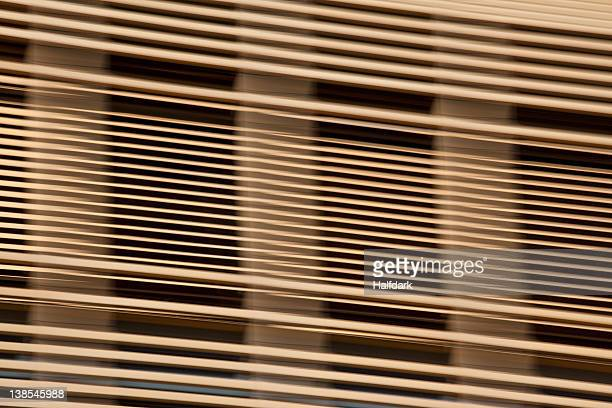 Louvered wooden slats in front of window