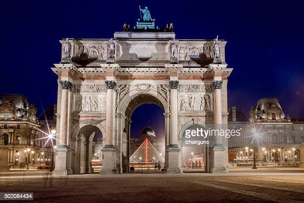 louvre museum through the triumphal arch - louvre pyramid stock photos and pictures