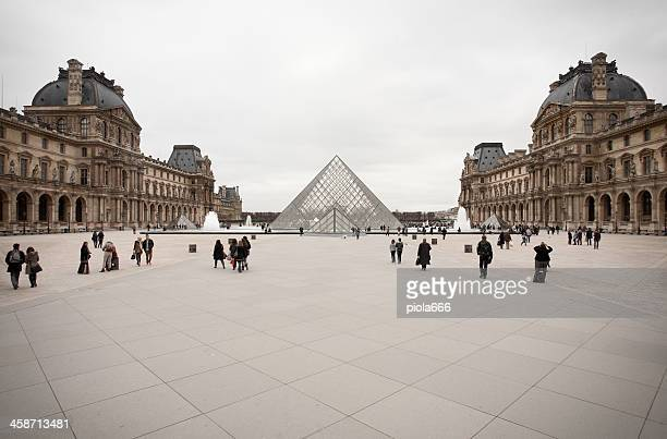 louvre pyramid and palace in paris - louvre pyramid stock photos and pictures