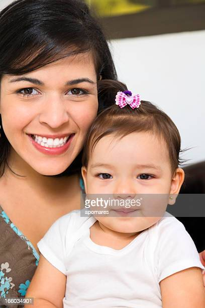 love and togethernes: young mother playing with baby girl - mexican and white baby stock photos and pictures