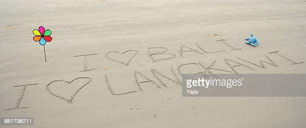 I love bali and langkawi written in sand on beach