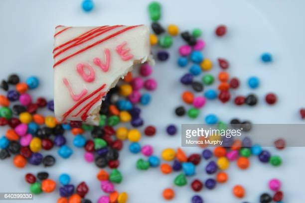 love cake on a plate with candy sprinkles with bite taken - love bite stock pictures, royalty-free photos & images