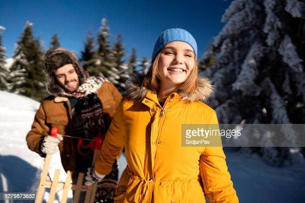 love couple on a sledding adventure - parka coat stock pictures, royalty-free photos & images