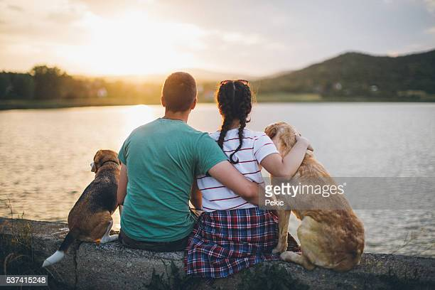 love couple with their dogs on the lake - sunset lake stock photos and pictures