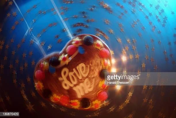 Love heart made of honey cake swinging on a broken string in circulating stars