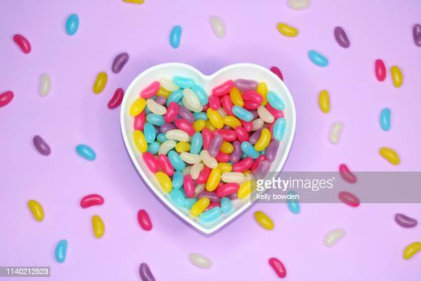 love heart shape jelly beans sweets candy background - sweet shop stock pictures, royalty-free photos & images