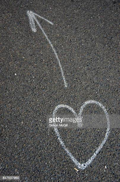 love heart symbol and arrow sprayed in white aerosol paint on a road in coffs harbour, new south wales, australia - following arrows stock pictures, royalty-free photos & images