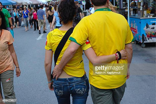 Love in Brazilian yellow! A couple wearing jeans and the infamous Brazil team color shirts walks arm around each other down Saint Laurent Street in...