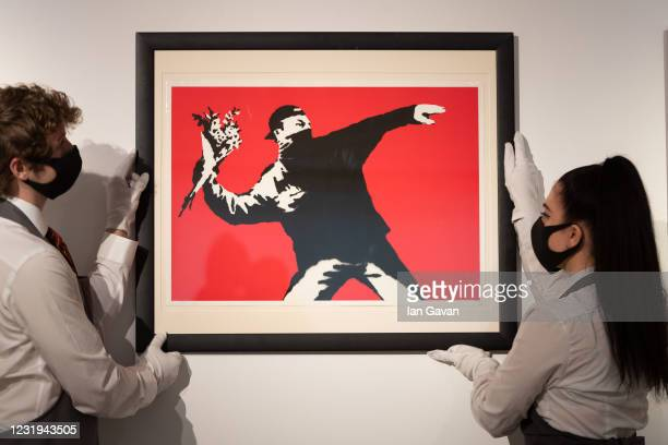 Love is in the Air by Banksy is displayed during preparations ahead of online sales at Christies Auction House on March 26, 2021 in London, England....