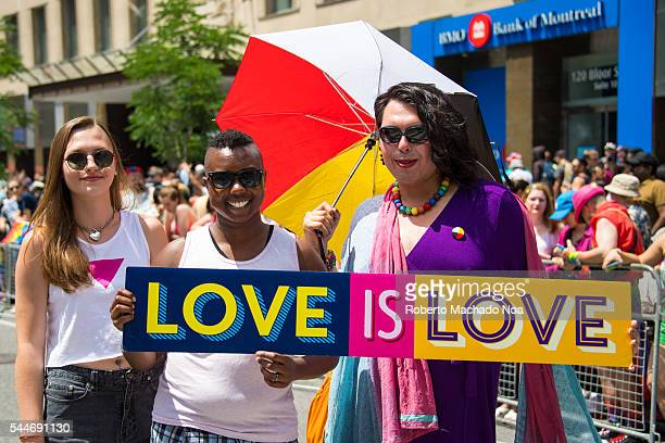 Love is Love sign held by multicultural attendees in the 36th Pride Parade