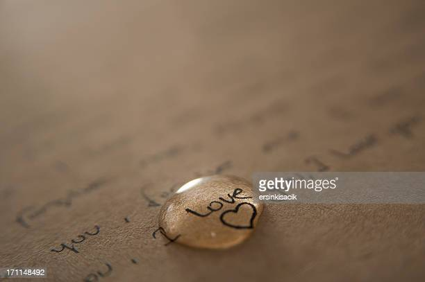 A love letter written on brown paper with a gold love heart