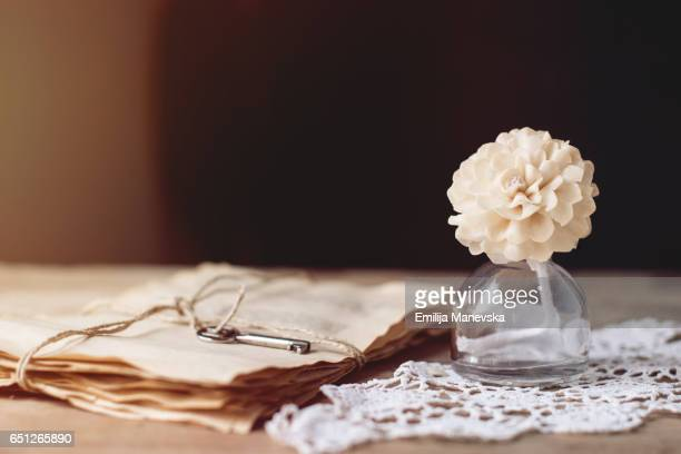 Love letters and white flower in a small glass bottle on a wooden table