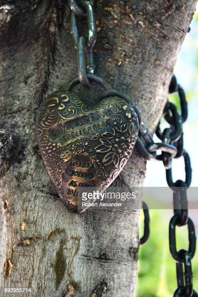 A love lock engraved with a couple's names is attached to a tree with a chain in the historic Plaza in Santa Fe New Mexico A love lock or love...