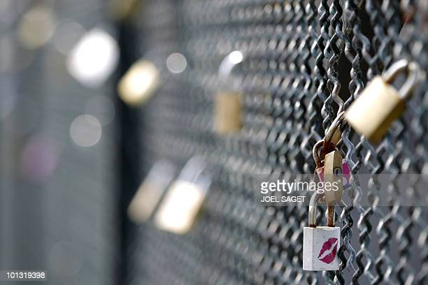 Love locks attached to a fence by lovers are pictured on the 'Pont des Arts' bridge in Paris on April 16 2010 AFP PHOTO JOEL SAGET