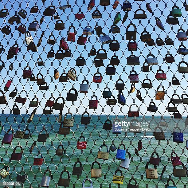 Love Locks Hanging On Chainlink Fence By Sea Against Sky