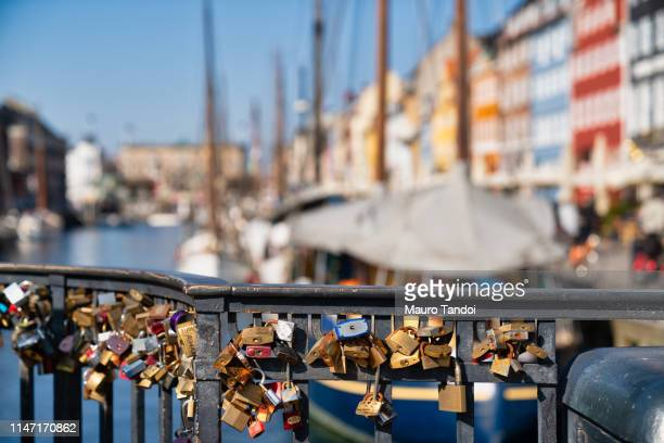 love locks hanging on the bridge in the foreground, nyhavn, copenhagen - mauro tandoi fotografías e imágenes de stock