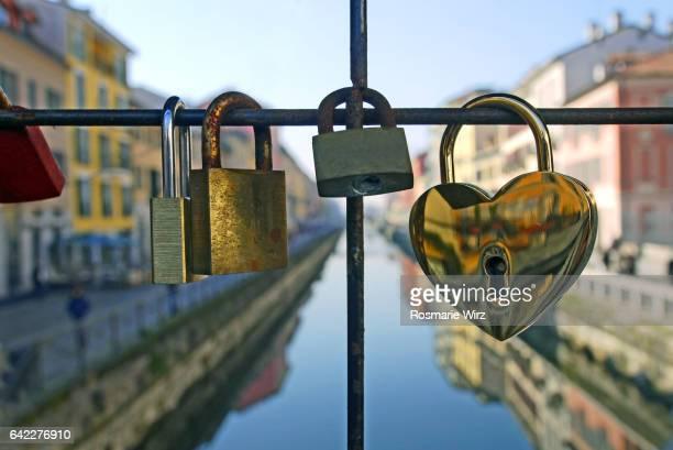 Love locks on footbridge railing on Naviglio Grande canal in Milan