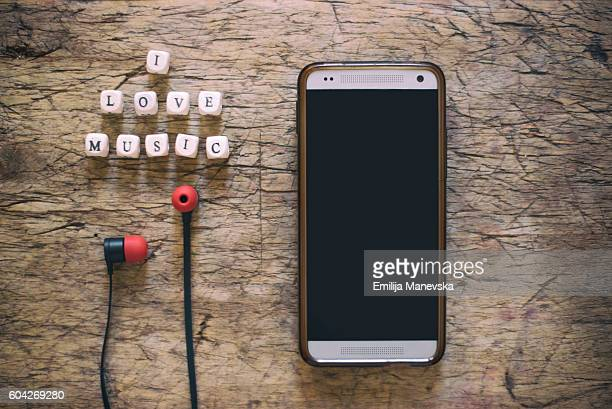 I love music word on wooden cubes, with cell phone and earphones