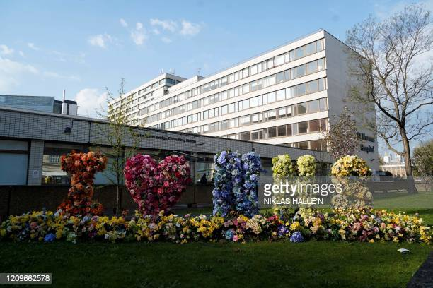 A 'I love NHS' sign is draped with flowering plants at St Thomas' Hospital in central London on April 11 where Britain's Prime Minister Boris Johnson...