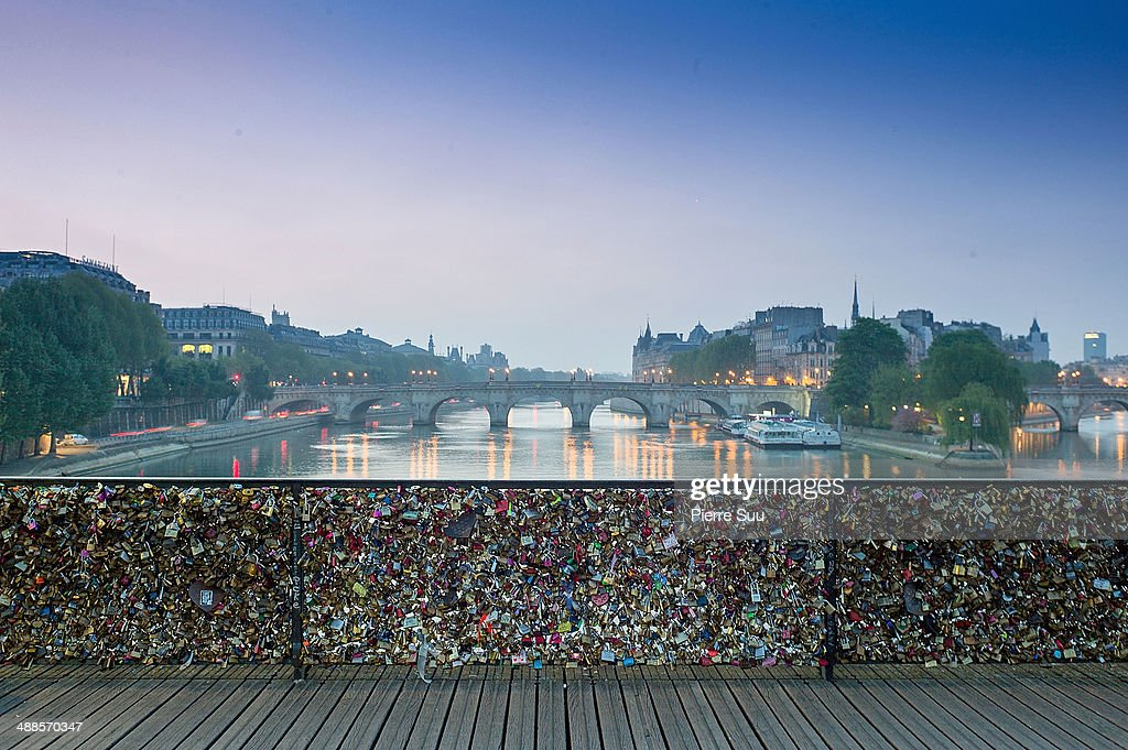 Love Padlocks on the Le Pont Des Arts bridge on May 7, 2014 in Paris, France. In recent years Le Pont Des Arts has attracted tourists who visit the bridge to attach padlocks to the railing or the gate with their names written or engraved on the padlock, and then throw the key into the river Seine as a romantic gesture. The accumulation of the 'love locks', a phenomenon popular in many European cities is starting to pose safety concerns, due to their mass weight.