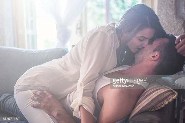 love passionate couple at sofa bed - erotiek stockfoto's en -beelden