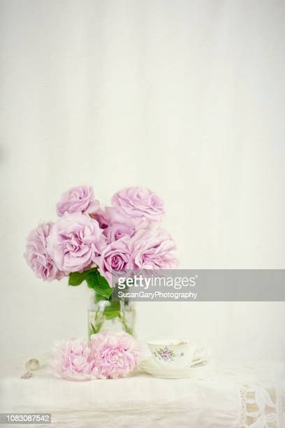 love song roses with peony and vintage tea cup - purple roses bouquet stock pictures, royalty-free photos & images