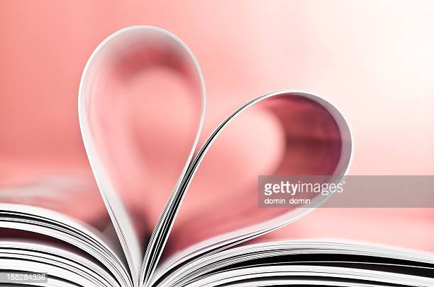 love to read, pages folded into heart shape, pink background - magazine page stock photos and pictures