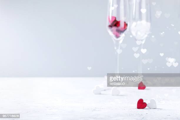 Love Valentine day greeting card with two empty champagne glasses and wooden hearts over white gray background Copy space Selective focus