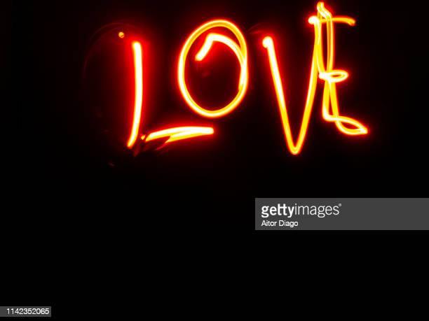 love written with red light on a black background - font stockfoto's en -beelden