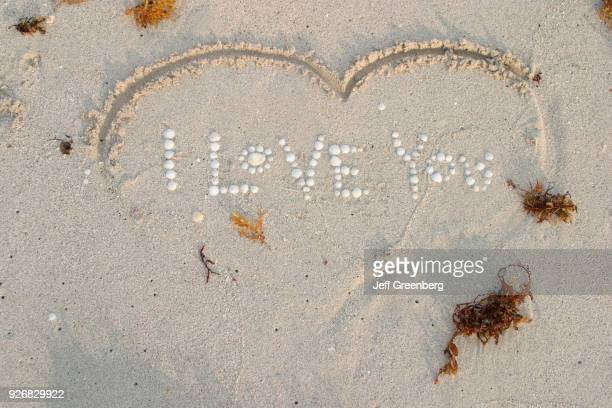 I Love You spelled out with shells in sand surrounded by shape representing a heart