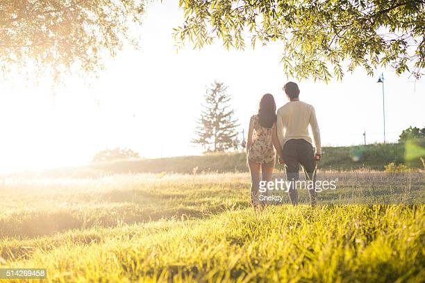 Love young couple holding hands and walking at park