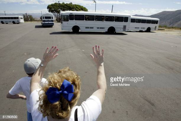 Loved ones wave to moving buses on September 11, 2004 at Camp Pendleton, California before the Third Battalion, 5th Marine Regiment departs in...