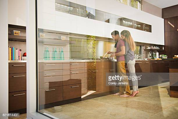 Loved up couple cooking on hob in kitchen